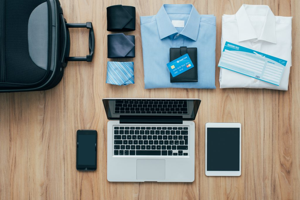 Planning a business trip: bag, formal clothing, credit cards and plane tickets on a desk with laptop, smartphone and tablet, traveling and technology
