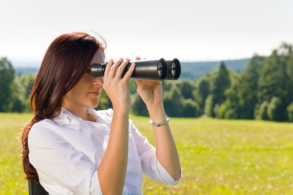 Business woman viewing outside with binoculars for p-card monitoring service